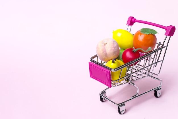 Carrello della spesa giocattolo in miniatura con un assortimento di frutta e verdura di grandi dimensioni colorate.