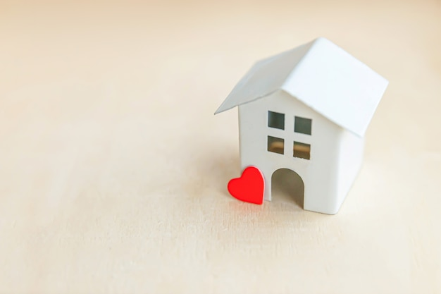 Casa modello giocattolo con cuore rosso su sfondo in legno. eco villaggio, sfondo ambientale astratto
