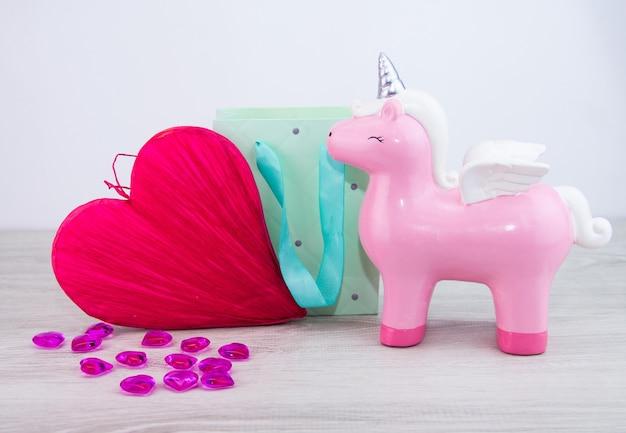 Un pegaso giocattolo si trova accanto a un grande cuore rosso. un regalo per una donna.
