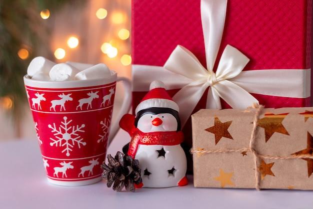 Un pinguino giocattolo, un regalo di natale, una tazza con decorazioni natalizie di marshmallow