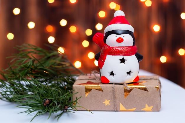 Un pinguino giocattolo sulla confezione regalo vicino al ramo dell'albero di natale sullo sfondo di bokeh sfocato