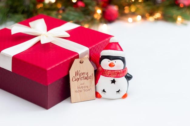 Un pinguino giocattolo una scatola regalo rossa una nota di legno con testo di congratulazioni decorazioni natalizie