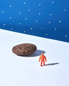 Giocattolo astronauta in plastica con pietra e ombre contro il cielo stellato blu. concetto di spazio esterno.