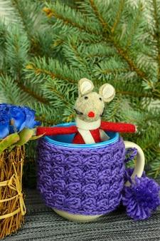 Ratto giocattolo sullo sfondo di rami di abete, fiori e tazze.