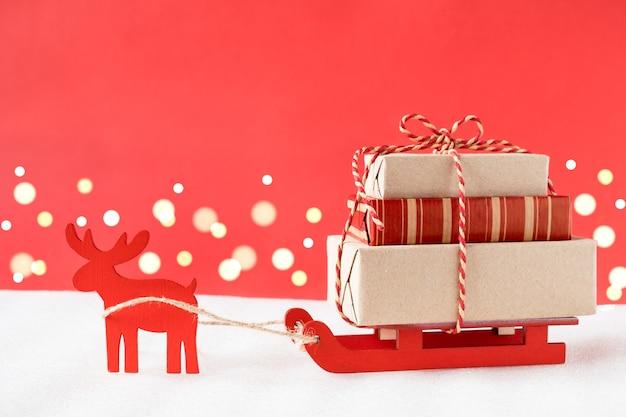 Renne giocattolo e slitta che consegna i regali di natale