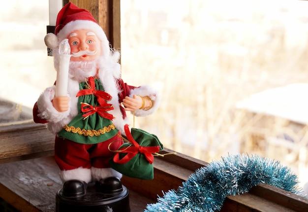 Babbo natale giocattolo in abiti rossi con una candela in mano