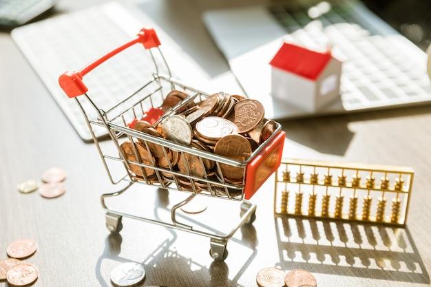 Carrello della spesa giocattolo pieno di monete su una scrivania