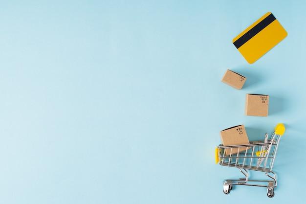 Carrello della spesa del giocattolo con scatole e carta di credito con lo spazio della copia