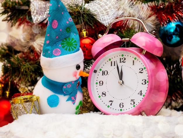 Un pupazzo di neve giocattolo vicino all'orologio, che mostra l'avvicinarsi delle 12 ore, il nuovo anno. pupazzo di neve, orologio vicino all'albero di natale_
