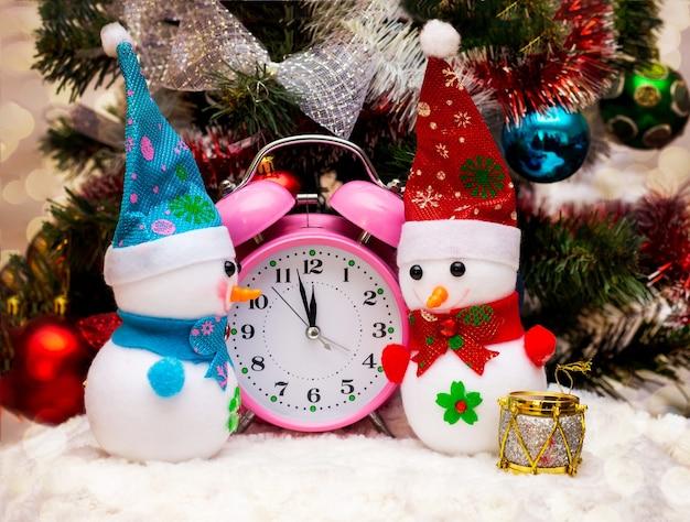 Pupazzo di neve giocattolo vicino all'orologio, che mostra l'avvicinarsi delle 12 ore, il nuovo anno. pupazzi di neve, orologio vicino all'albero di natale_