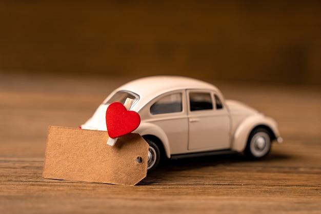 Una macchinina bianca con un cuore con un pezzo di carta per appunti su uno sfondo di legno