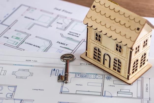 Casa in legno giocattolo con chiave sul progetto architettonico