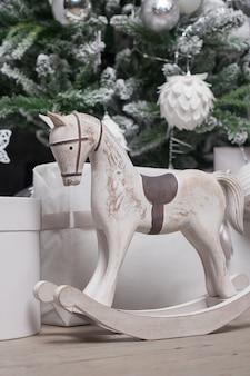 Cavallo a dondolo di legno del giocattolo nell'interiore di natale.