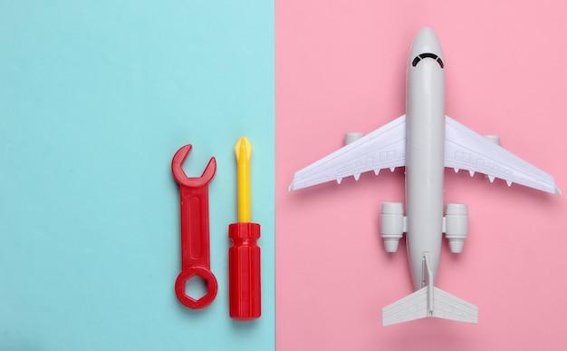 Attrezzi da lavoro giocattolo e aeroplano su un blu-rosa
