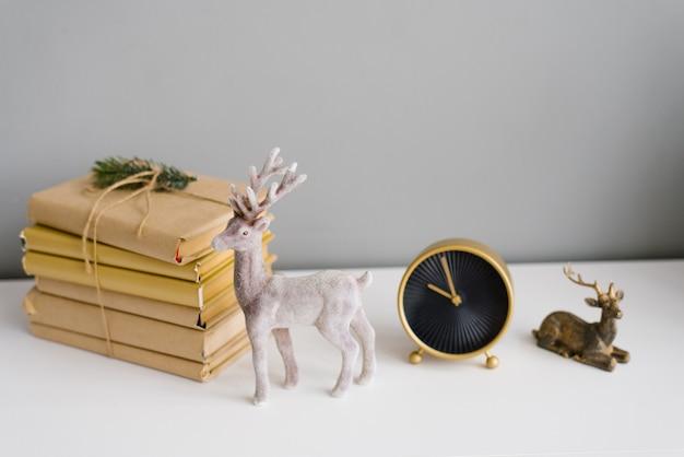 Giocattoli souvenir renne di natale, una pila di libri e un orologio da tavolo nell'arredamento della casa