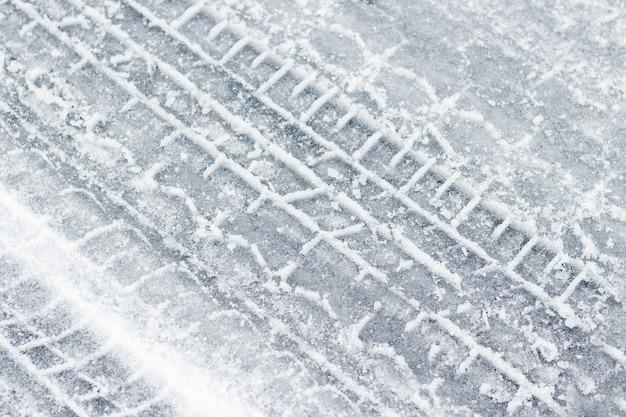 Tracce dell'auto su una strada innevata in inverno Foto Premium