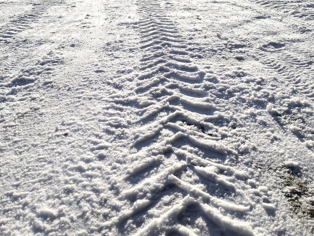 Tracce di pneumatici per auto nella neve alla luce del sole splendente.