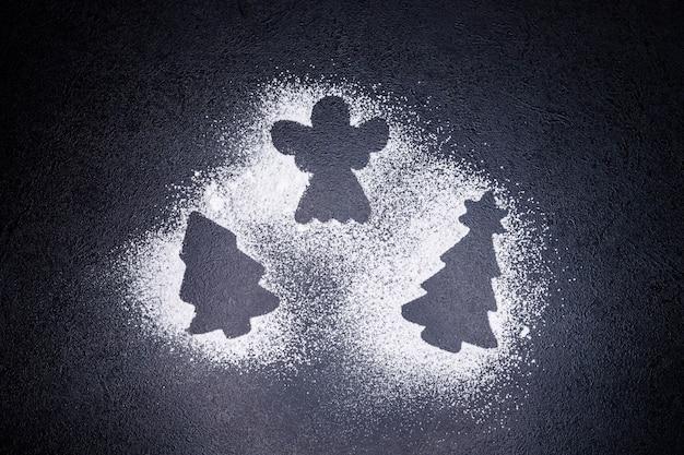 Tracce da uno stampino a forma di albero di natale e angelo con fiocchi di neve di farina
