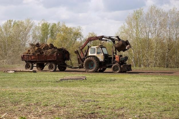 Trattore e letame carico di carrello. vita di campagna