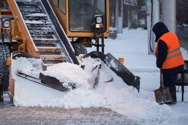 Trattore che pulisce la strada dalla neve. l'escavatore pulisce le strade da grandi quantità di neve in città. i lavoratori spazzano la neve dalla strada in inverno.