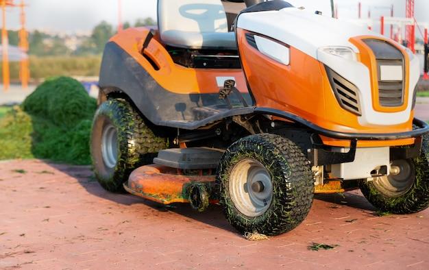 Primo piano del tosaerba del trattore sullo sfondo di un mucchio di erba falciata nel parco.