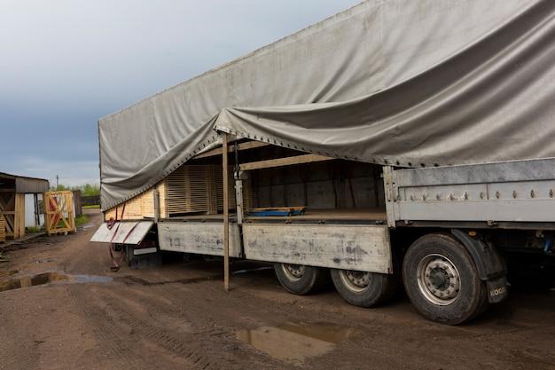 Il trattore carica tavole, legname dal magazzino del prodotto finito nel container del camion. foto di alta qualità
