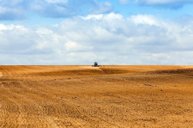 Trattore che ara il campo agricolo