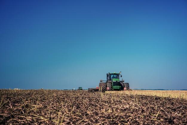 Trattore che ara il campo dell'azienda agricola in preparazione per la semina della molla Foto Premium