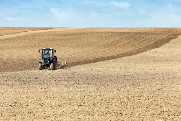 Un trattore che ara un campo situato nel terreno durante la semina.