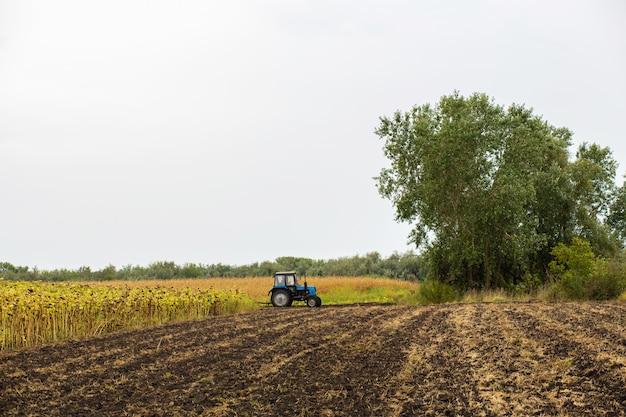 Un trattore ara un campo con un aratro. paesaggio rurale di un paese agricolo. seminare la stagione