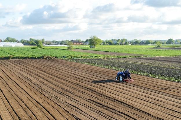 Un trattore viaggia su un campo di fattoria.