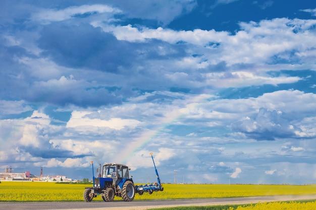 Il trattore gira vicino al campo con un arcobaleno