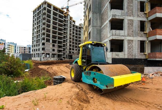 Il rullo del trattore compatta il terreno per la costruzione di una nuova strada sullo sfondo di una nuova casa