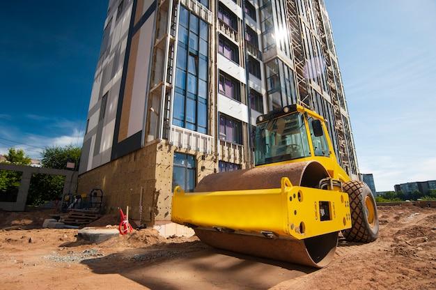 Il rullo del trattore compatta il terreno in una nuova casa in costruzione