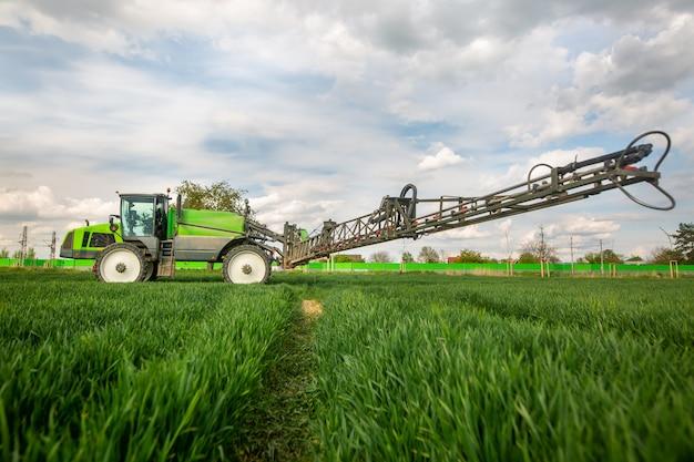 Trattore irrorazione di pesticidi, fertilizzazione sul campo vegetale con irroratore a primavera, concetto di fertilizzazione