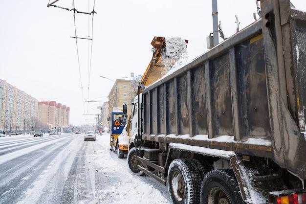 Auto trattore e ribaltabile pulizia delle strade di grandi quantità di neve in città dopo la tempesta di neve