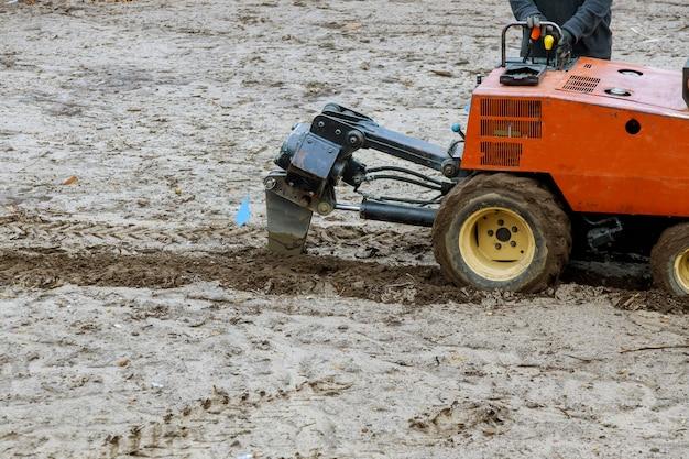 Trattore utilizzato per lavori di sterro di condotte a scavo di un terreno con giardino a terra per impianto di irrigazione