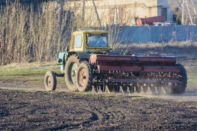 Un trattore con un coltivatore torna con una campagna di semina lungo una strada di campagna. il trattore ha bloccato completamente la strada. i grandi mezzi di trasporto passano lungo la strada.