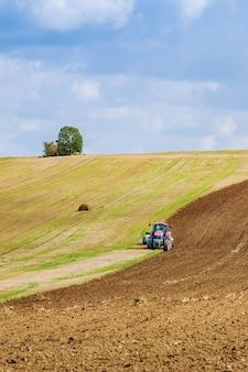 Un trattore con un grande aratro ara un campo. trattore con attacco agricolo. preparazione del terreno per la semina.