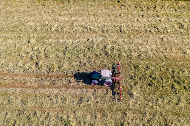 Trattore con voltafieno, vista aerea dall'alto, agricoltura e allevamento
