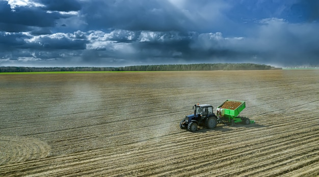 Trattori al lavoro in un campo che coltiva il terreno pronto per la semina delle patate. vista aerea.