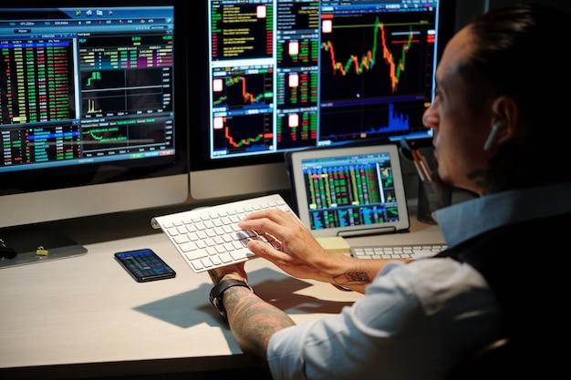 Trader che lavora fino a tarda notte, compra e vende azioni e investe in futures