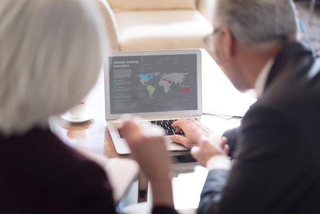 Commercianti al lavoro. colleghi anziani coinvolti e concentrati che guardano il laptop e si siedono in ufficio mentre discutono del progetto ed esprimono interesse