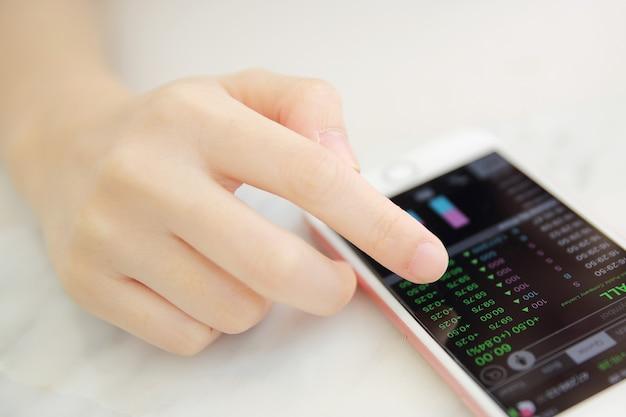 Trading online su smartphone con la mano di una donna d'affari
