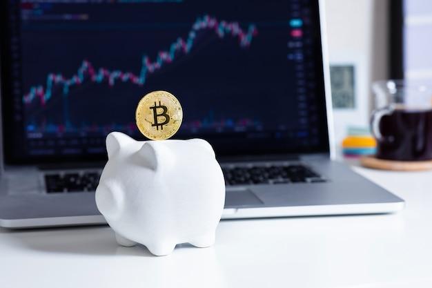 Scambiare o risparmiare criptovaluta con bitcoin e salvadanaio e sfocatura del prezzo del grafico sul computer