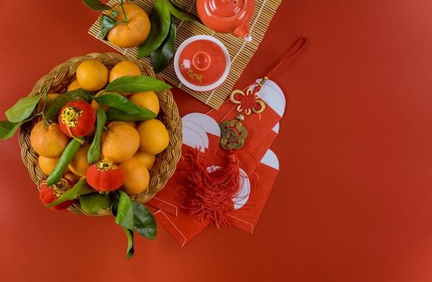 Tradizione delle celebrazioni del capodanno asiatico di decorazione con set da tè da cerimonia, mandarini nelle buste rosse