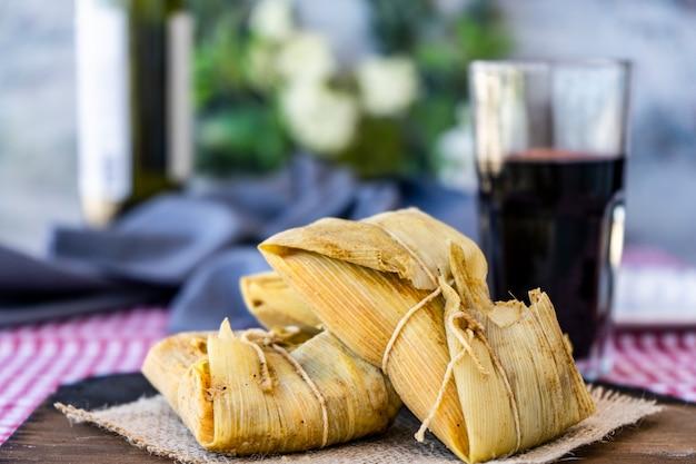 I tradizionali tamales andini di mais e carne serviti su una tavola di legno su un tavolo di natura morta con vino