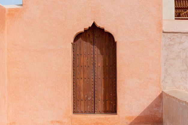 Architettura araba tradizionale, porta di legno in stile musulmano e muro di argilla rossa