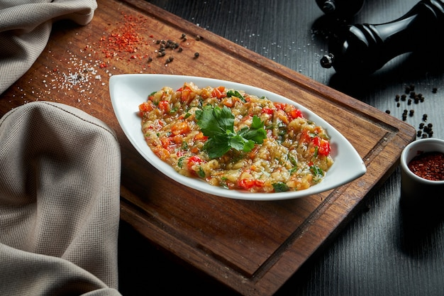 Piatto tradizionale arabo di melanzane baba ghanoush con olio d'oliva ed erbe aromatiche. tavolo in legno. avvicinamento