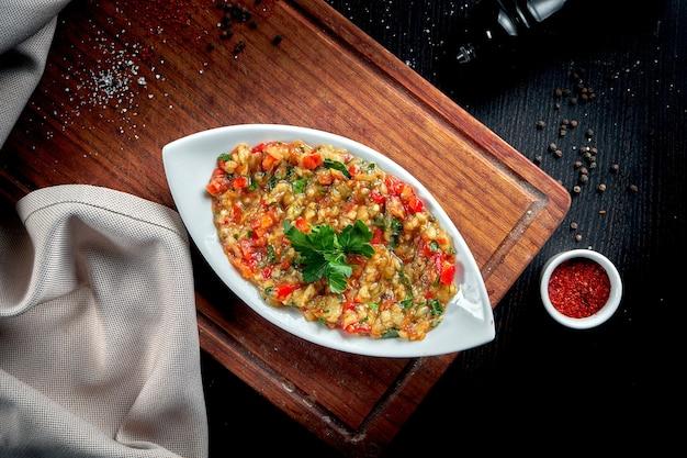 Piatto di melanzane arabo tradizionale baba ghanoush con olio d'oliva ed erbe sulla tavola di legno